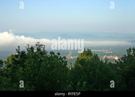 A long, low lying cloud bank hovers over a small city in the Appalachian Mountains - Stock Image