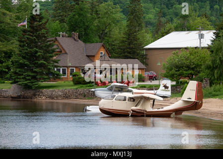 Two seaplanes, a Republic RC-3 and a Cessna 180J tied up on the beach on Lake Pleasant in Speculator, NY in front of the Lake Pleasant Lodge. - Stock Image