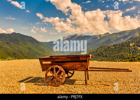 Nice vintage wooden cart with ocean coastline background, Oia, Santorini, Greece,wooden cart on the background of mountains - Stock Image