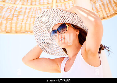 A young pretty woman holding her hat on the beach - Stock Image
