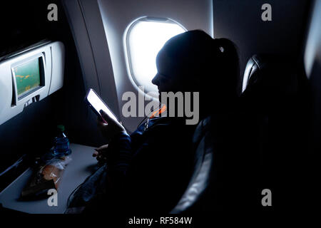 Woman in silhouette by window in Jet Blue plane - Stock Image