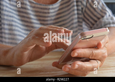 Woman seated at a table using a smartphone, close-up of hands and phone, midsection view - Stock Image