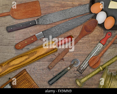 vintage bakery shop tools and utensils over stained wooden table - Stock Image