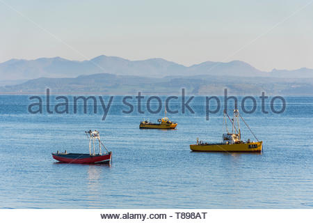 Morecambe, Lancashire, UK, 12th May 2019, UK Weather. Boats moored in Morecambe Bay in the early morning sunshine with the Coniston and Langdale Fells visible in the distance across Morecambe Bay. After an overnight ground frost and a cold start to the day, unbroken sunshine is forecast, with temperatures rising into the early part of next week. Credit: Keith Douglas News/Alamy Live News - Stock Image