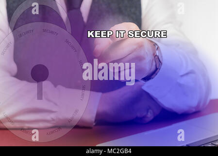 Business man sitting at desk pressing a KEEP IT SECURE on a screen . - Stock Image