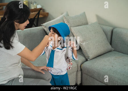 kid kiss her mother's hand before going to school. asian kindergarten student with backpack and uniform back to school - Stock Image