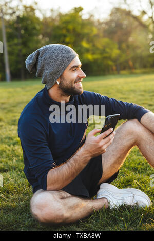 Image of a happy handsome young strong sports man wearing hat posing outdoors at the nature park location resting sitting listening music with earphon - Stock Image