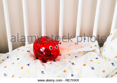 Poznan, Poland - November 8, 2018: Red transparent plastic piggy bank on a wooden baby bed. - Stock Image