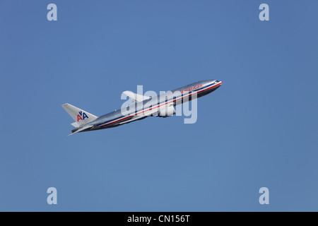 American Airlines Boeing 777-223/ER N799AN climbing away from Heathrow airport - Stock Image