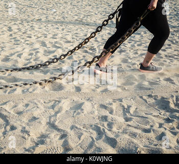 A woman drags a metal chain as part of a bootcamp fitness session on Falmouth's Gyllyngvase Beach. - Stock Image