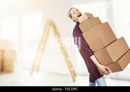woman moving into new apartment holding stack of cardboard boxes - Stock Image
