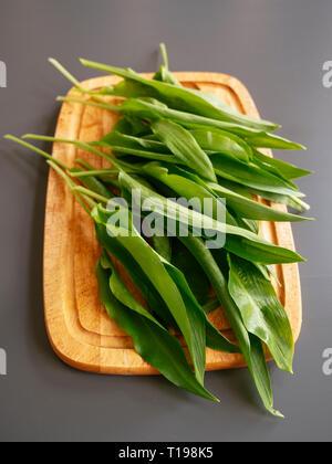 Fresh wild garlic leaves on a cutting board. - Stock Image