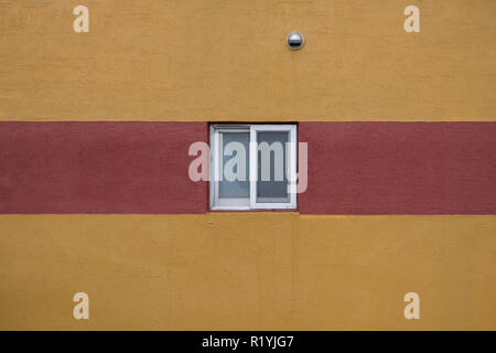 Single small square window and minimal red stripe on yellow wall abstract - Stock Image