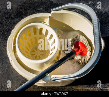 Overhead shot of a mop lying in a plastic bucket containing clean, soapy water, outside in the sunshine. - Stock Image