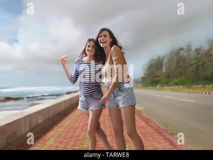 Two women walking together on road beside sea - Stock Image