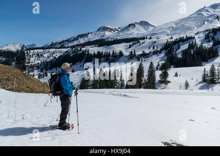 Middle-aged male snowshoe hiker in the Swiss Alps, enjoying the sun and panorama of the surrounding mountains. Stoos, - Stock Image