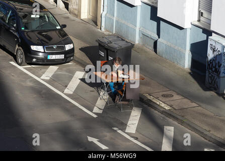 Man sitting in the sun on a table on the street - Stock Image
