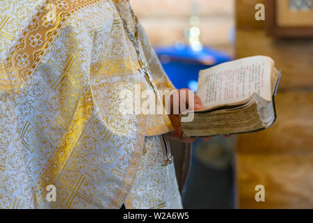 Book is in the hands of a priest - Stock Image