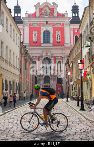 Travel bike, a male cyclist riding his bicycle through Poznan Old Town in Poland glances at the Baroque facade of the Parish Church of St Stanislaus. - Stock Image