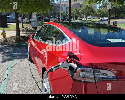 Red Tesla Model three (3), parked and charging at an electric vehicle or electric car charging station on the street in Montgomery Alabama, USA. - Stock Image