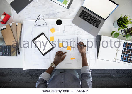 View from above male architect editing blueprints at desk - Stock Image