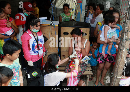 Manila, Philippines. 16th Feb, 2019. A child receives a free measles vaccine during the Philippine Red Cross Measles Outbreak Vaccination Response at a slum area in Manila, the Philippines, Feb. 16, 2019. The Philippine Department of Health (DOH) reported this week that over 4,300 measles cases were confirmed from Jan. 1 to Feb. 13, 2019, with the number expected to increase in the coming days. Credit: Rouelle Umali/Xinhua/Alamy Live News - Stock Image