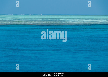 A view of the horizon on the Great Barrier Reef, Australia. The blue water in the bottom part of the frame is deeper - Stock Image