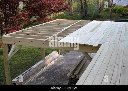 Construction of an exterior wooden deck in springtime with the framing done and boards nailed down across half of it creating a platform. - Stock Image