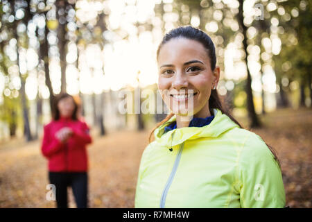 A portrait of young female runner standing outdoors in forest in autumn nature. - Stock Image