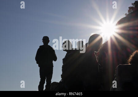 Hikers in silhouette against the sun on Mount Tryfan mountain in Snowdonia. Ogwen, North Wales, UK, Britain - Stock Image