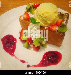 Honey toast with vanilla ice cream, sliced kiwi and strawberries, whipped cream and cranberry sauce. Vintage painterly - Stock Image