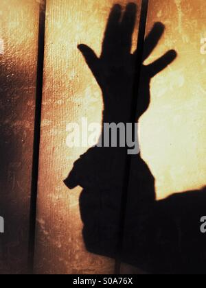 A man casting a shadow on a wall, counting on his hand. Number five. - Stock Image