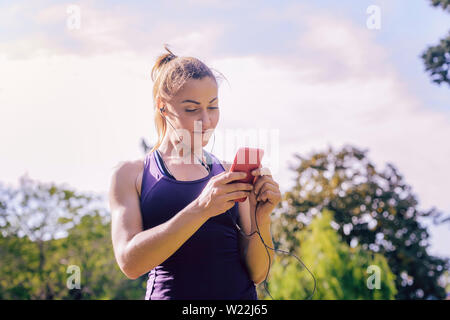 attractive blonde sporty woman setting up phone app before workout outdoors at park, fitness accessories - Stock Image