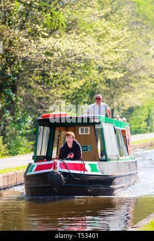 Front view of a narrow boat moving along the Shropshire Union Canal, UK. Canal boat and people back lit on a sunny spring day. - Stock Image