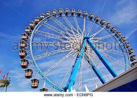 Ferris wheel and roller coaster at Oktoberfest, Munich, Germany - Stock Image