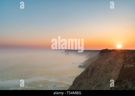 Misty sunrise over the sea and cliffs near Hayle Cornwall - Stock Image
