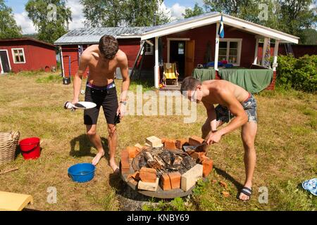Brothers grilling fish, Northern Sweden. - Stock Image