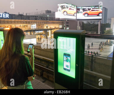 Someone using a smartphone whilst waiting for a train on a platform at Siam station in Bangkok Thailand - Stock Image