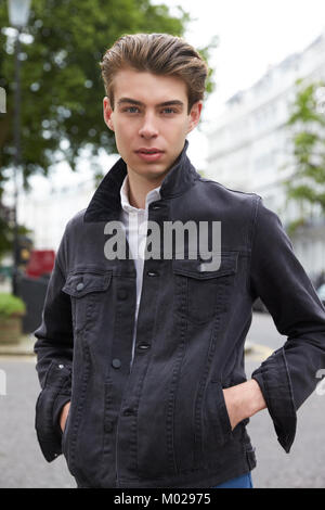 Young man in black denim jacket with hands in pockets - Stock Image