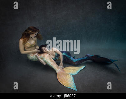 Two mermaids at bottom of pool - Stock Image