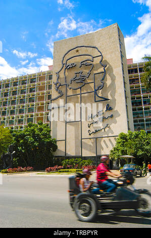 Mototorbike speeds by Che Guevara's metal image on the Ministry of Interior Building, Plaza de la Revolucion, Havana, Cuba, Caribbean - Stock Image