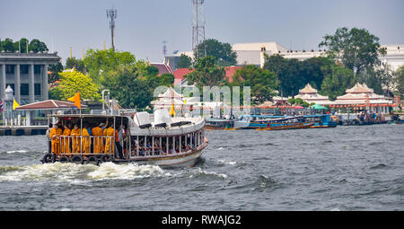 Monks in a boat in the Chao Praya River in Bangkok in Thailand - Stock Image