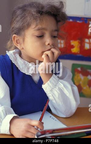 contemplative little primary schoolgirl sitting at desk - Stock Image