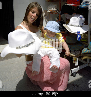 Mother and toddler shopping for hats, Mijas Pueblo, Costa del Sol, Andalucia, Spain - Stock Image