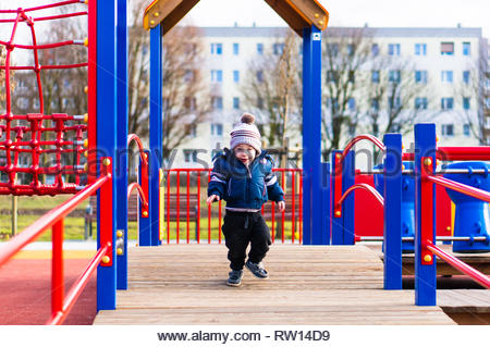 Poznan, Poland - February 24, 2019: Young toddler boy in warm clothes running on a wooden platform with red barriers of a equipment in a playground on - Stock Image