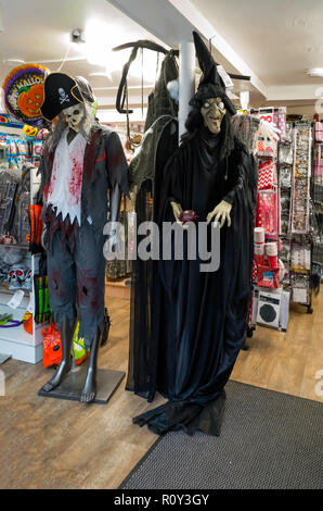Seasonal Fancy Dress costumes for sale at Halloween one depicting a pirate and the other a witch - Stock Image