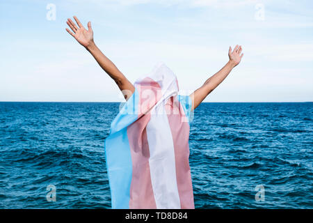 a young caucasian person covered with a transgender pride flag with his or her arms open in the air, with the ocean in the background - Stock Image