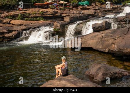 Cambodia, Koh Kong Province, Tatai, Waterfall, western tourist sat on rocks overlooking falls in dry season - Stock Image