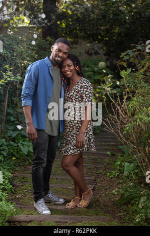 An African couple standing together in a garden - Stock Image