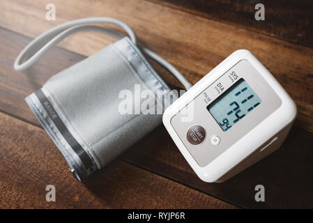 Sphygmomanometer an electronic blood pressure monitor on a wooden table. concept of health and medical - Stock Image